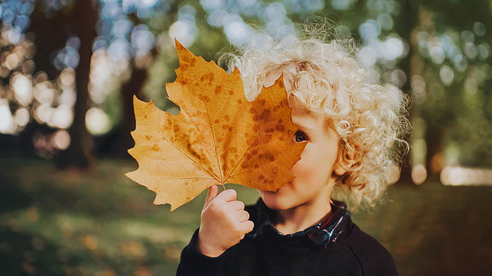 10 easy ways to boost your mood this autumn child looking from behind leaf