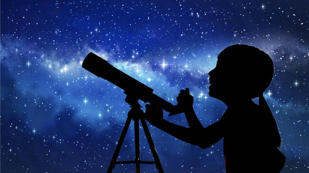Child and telescope silhouette against a star background