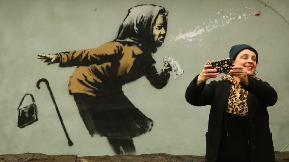 Socially distanced days out woman taking photo next to Banksy picture