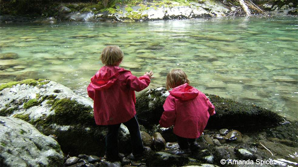 Backpacking with kids: children playing by a river
