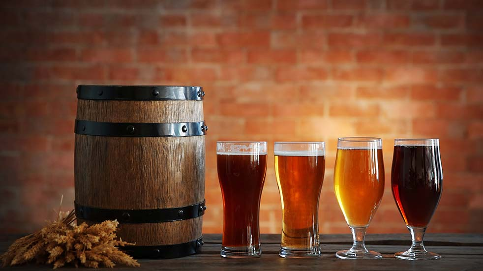 A photo of four glasses filled with craft beers next to a keg