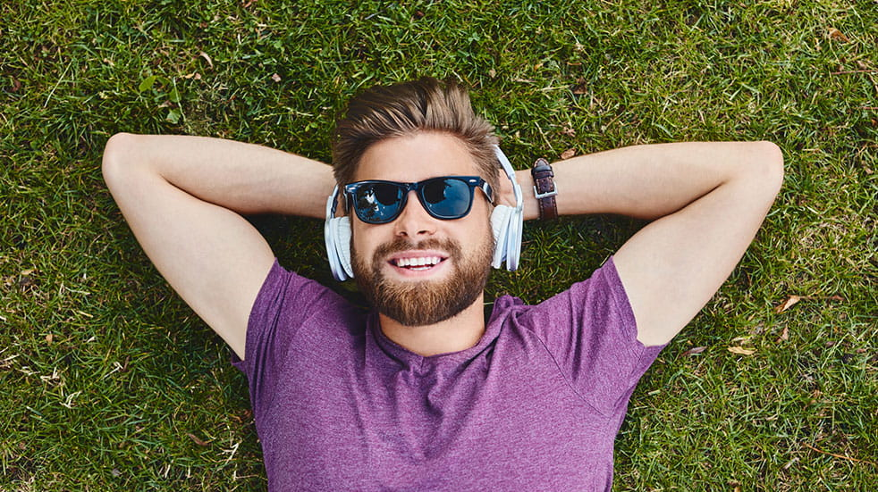 Best summer podcasts man lying on grass wearing headphones