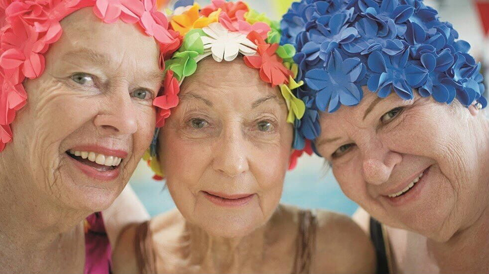 3 older ladies with floral swimming caps on