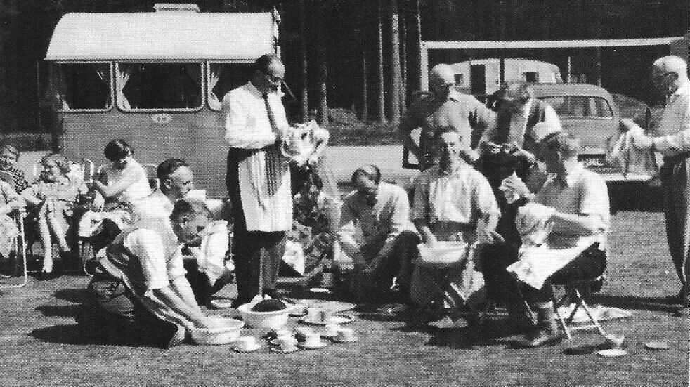 Black and white photo of the 1960s camping and caravanning group having a picnic outside