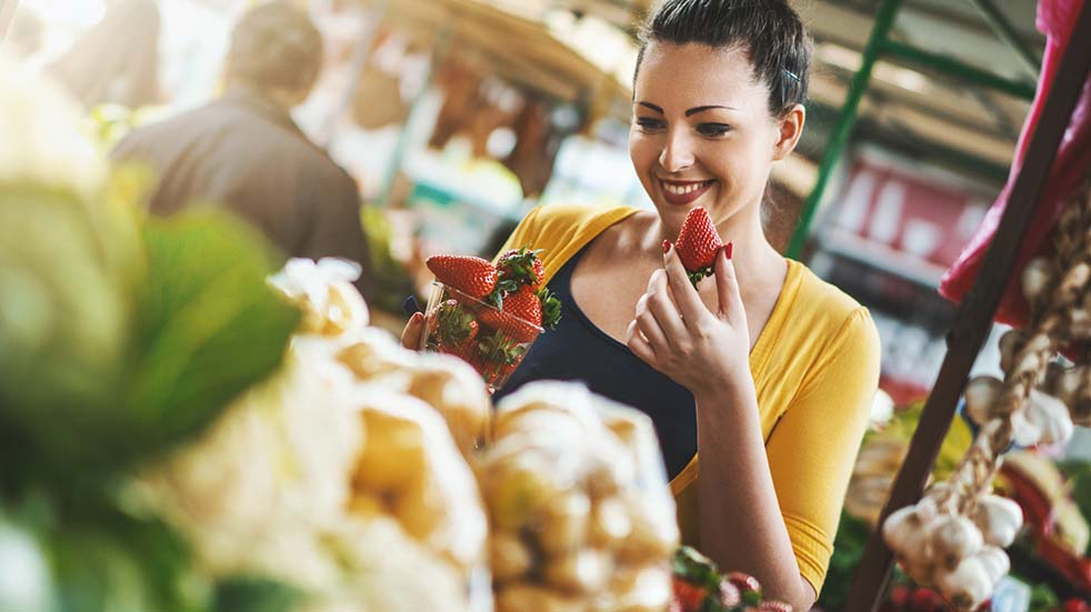 British Food and Drink Fortnight woman smiling eating strawberry