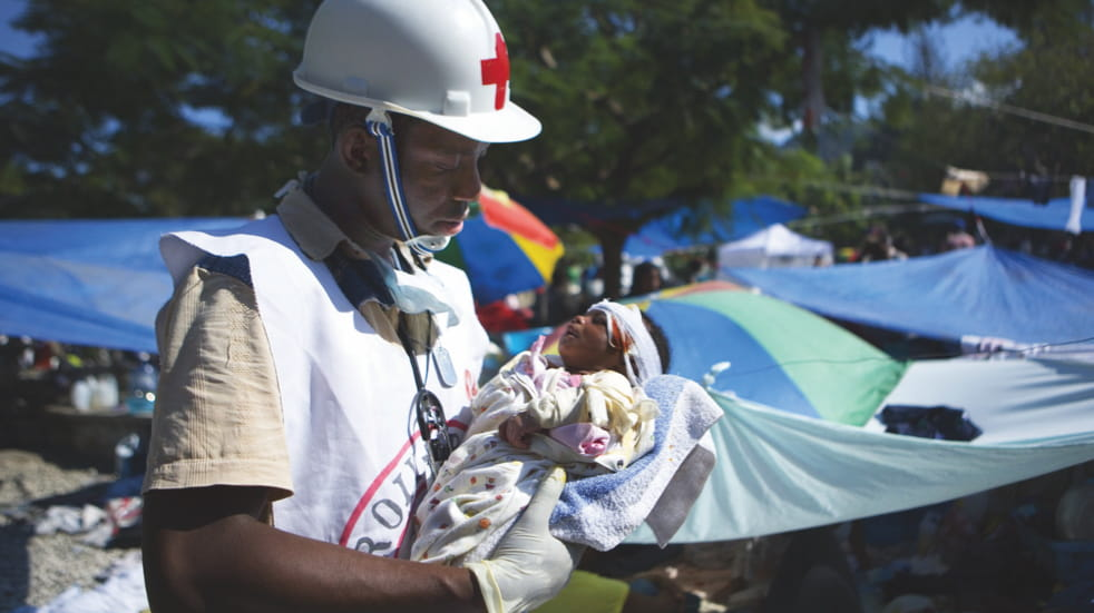 A British Red Cross worker cares for a baby
