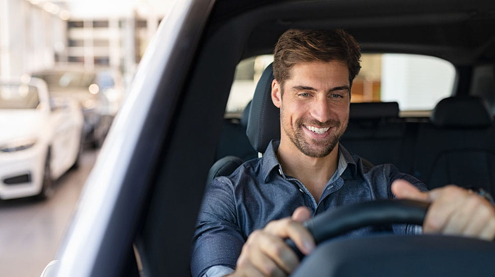Buying an EV man smiling while driving car
