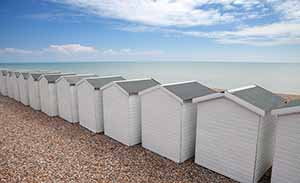 White beach huts on the English channel between Hastings and Eastbourne