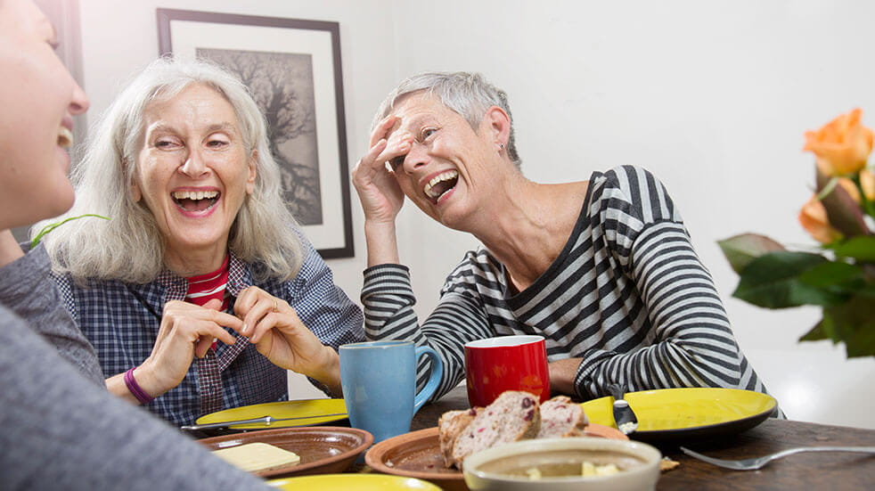 3 women laughing in a cafe over coffee