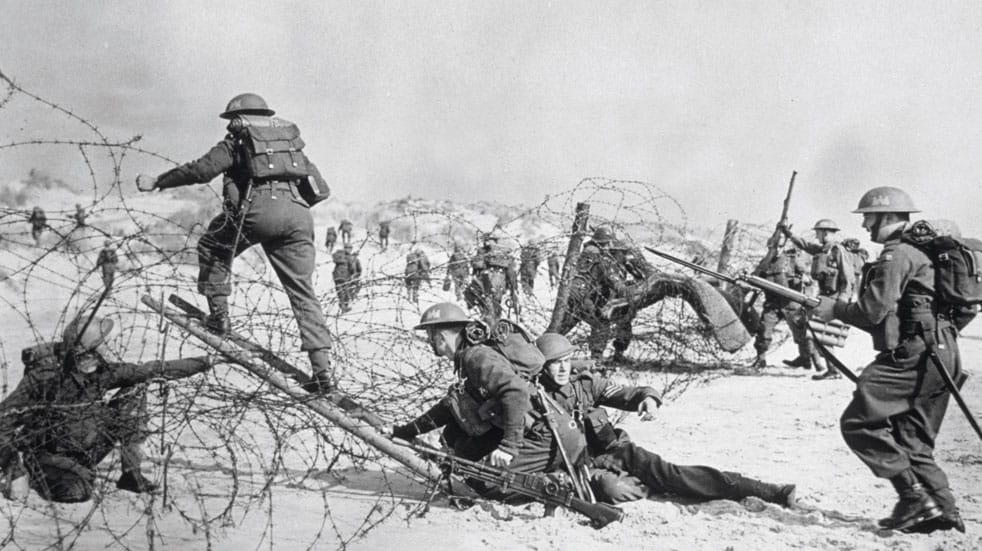 Soldiers carry out a training exercise across barbed wire
