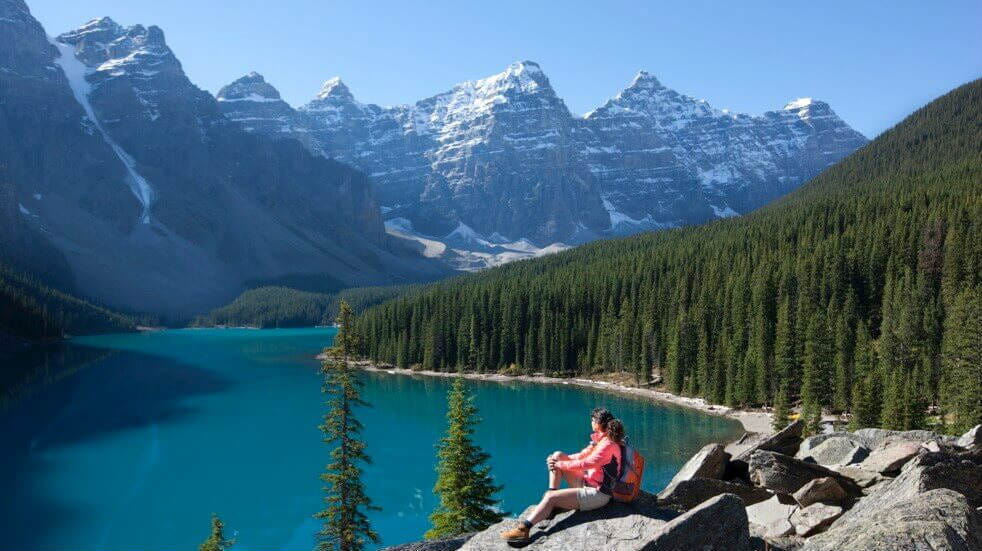 Hiker in Moraine Lake mountains in Alberta, Canada