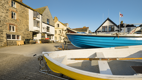 Photo of a yellow and blue boat moored outside of houses