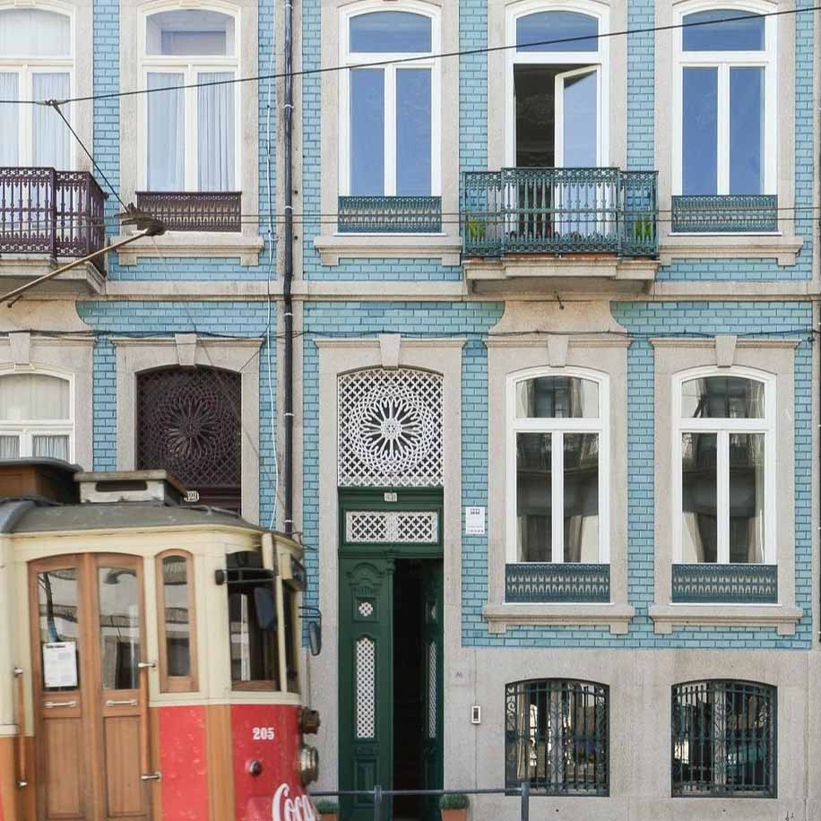 Old-fashioned tram passing by town houses in Porto