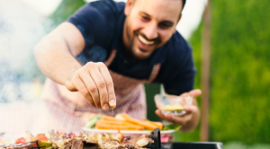 Fantastic outdoor things you can buy this spring and summer man adding food to barbecue