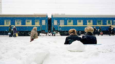 Passengers sit on a bench in the heavy snow, as the Trans-Siberia Express pulls into a station