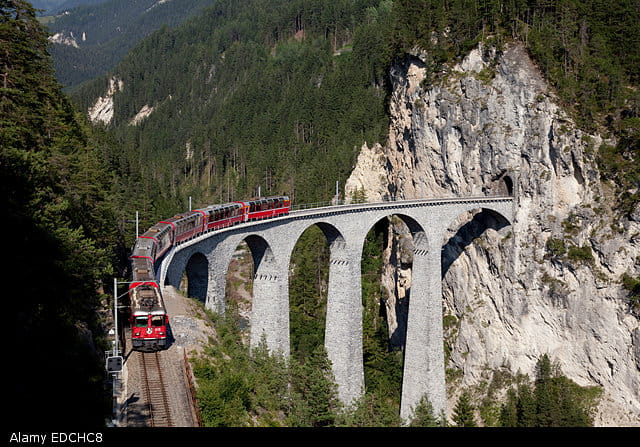 Red train crosses huge viaduct on Switzerland's Glacier Express route