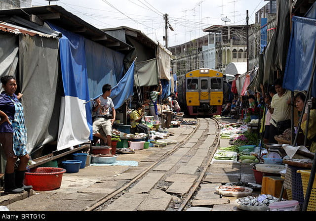 Thailand's Maeklong Railway inches its way through a market, with stalls on either side of the rails