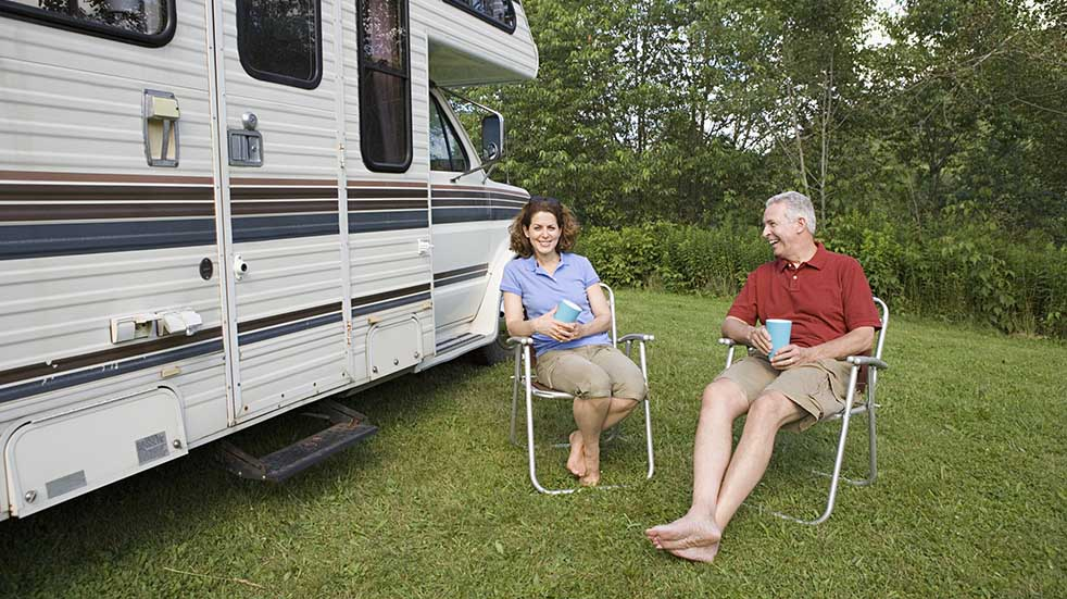 Have a safe and happy holiday couple sitting by motorhome