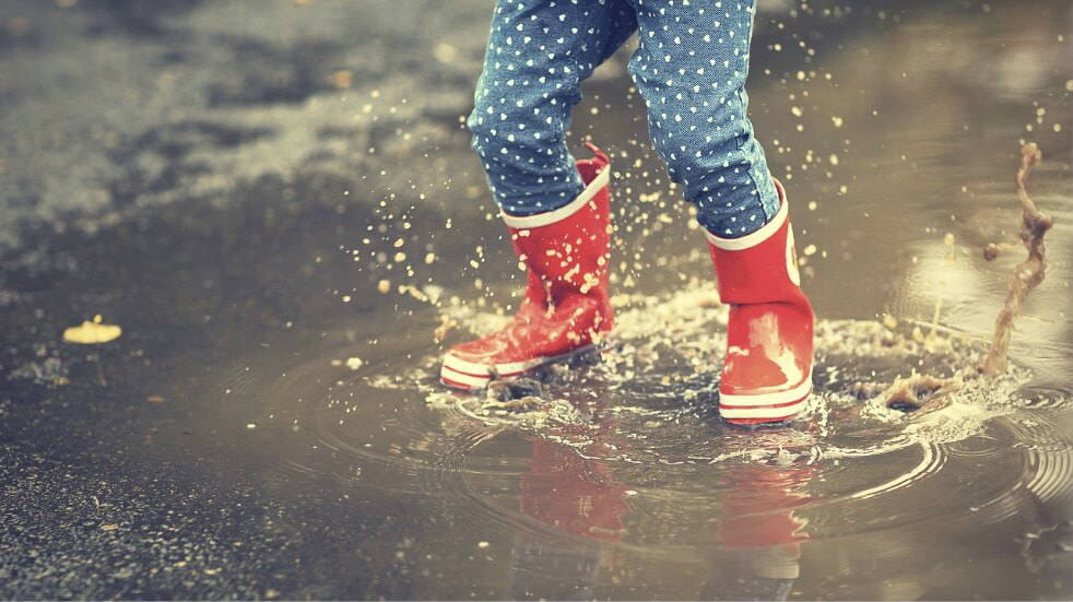 Child in red wellies jumping in a puddle