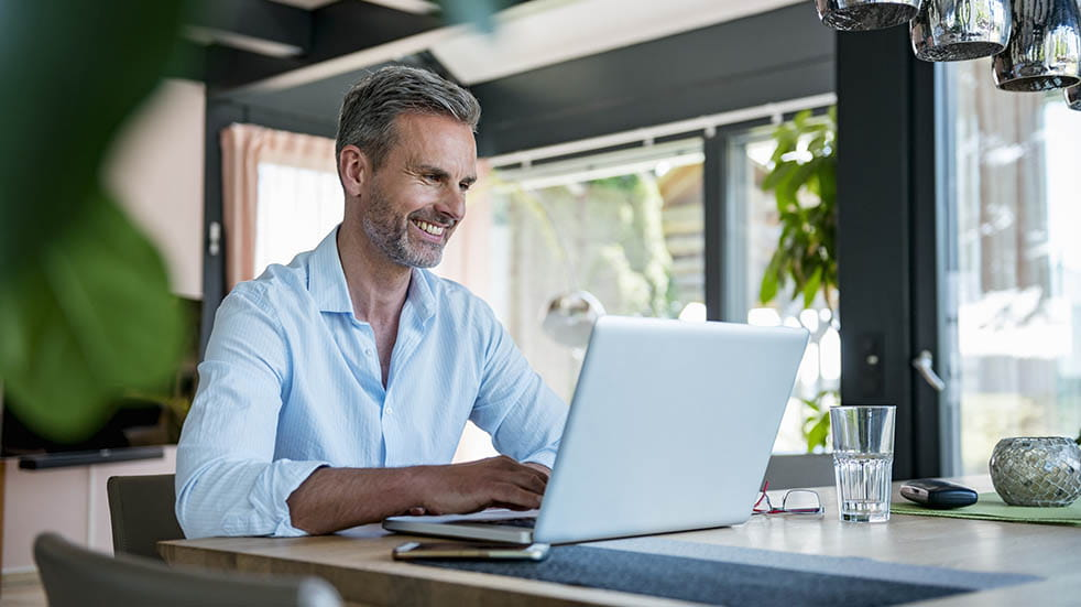 Working from home; man smiling with laptop