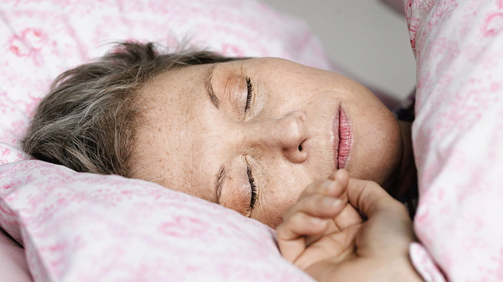 How to train yourself to sleep better; woman in pink bed