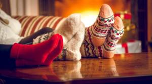 Feet with festive socks on up on a table in front of a fireplace
