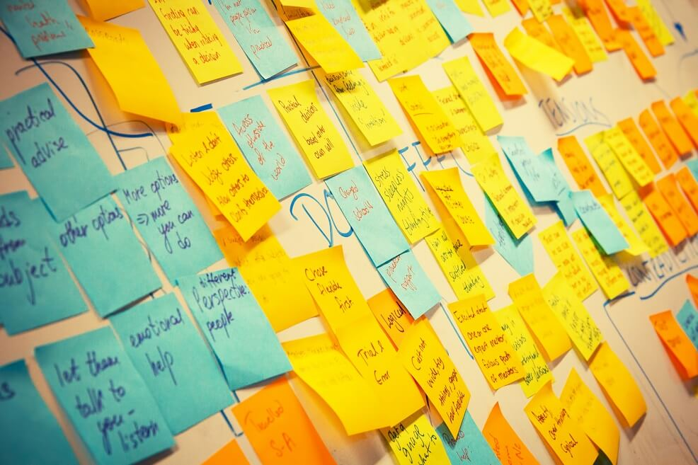 Noticeboard covered with hundreds of yellow post-it to-do notes on it