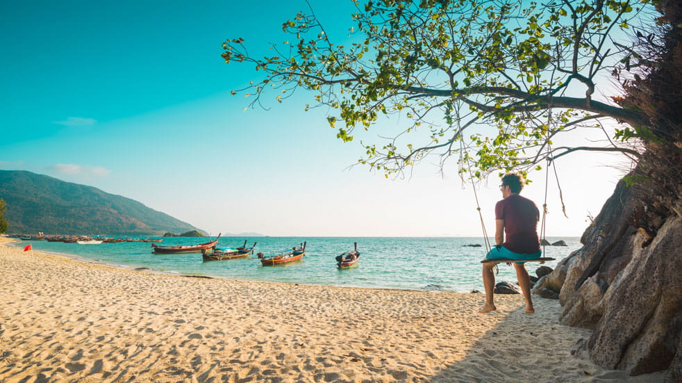 A man sits in a tree swing looking out over boats on a beach in Thailand