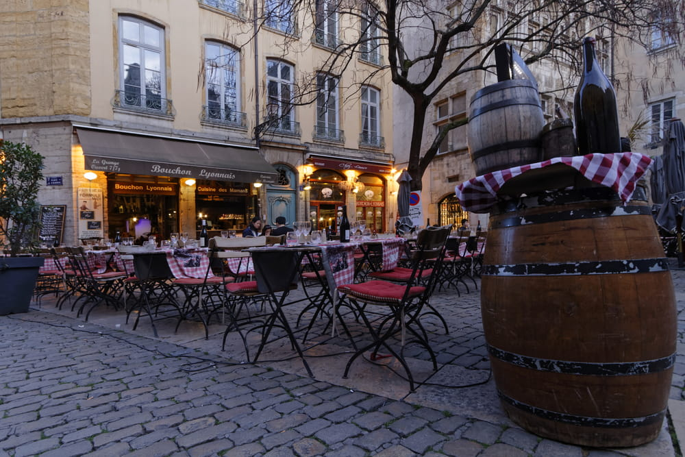 Cosy scene of tables outside a 'bouchon' restaurant at twilight in Lyon, France