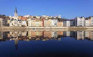 View of riverside Lyon, with the town's pretty waterside buildings reflected in the water