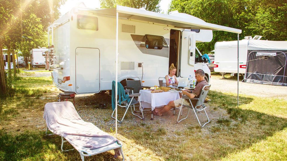 Plan your first motorhome holiday; couple relaxing outside motorhome