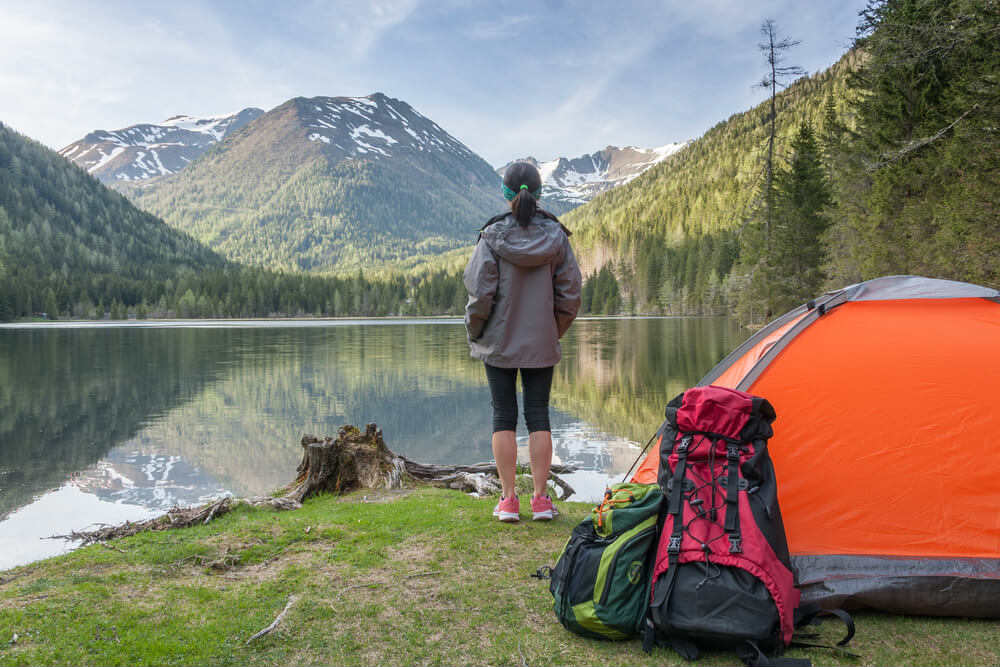 Woman looking over a lake with camping gear behind her