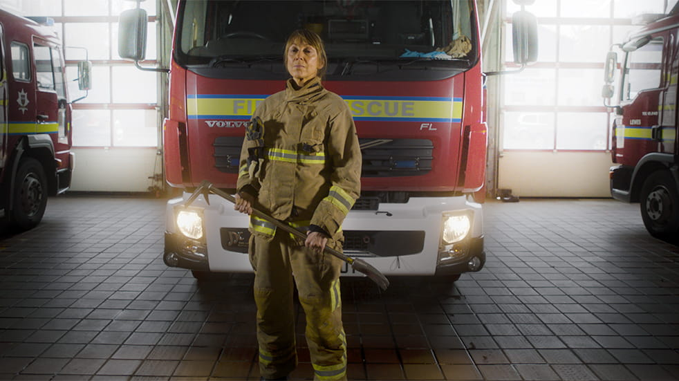 Public Service Day: female fire fighter with fire engine, women in the public sector
