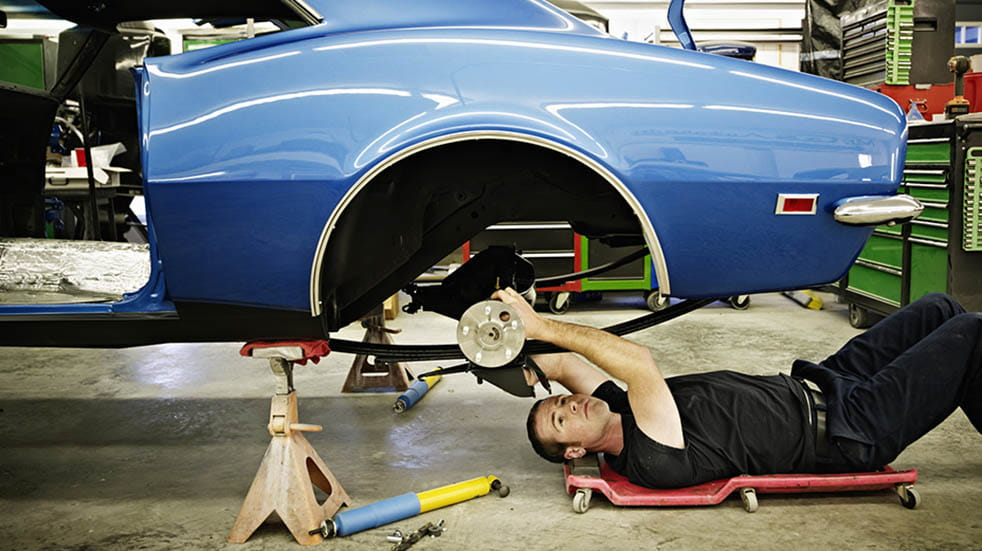 Restoring a classic car; man on floor