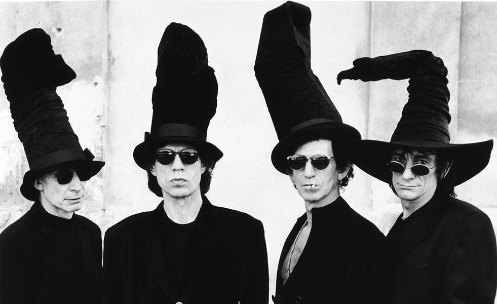 Charlie Watts, Mick Jagger, Keith Richards and Ronnie Wood of the Rolling Stones wearing comically large and floppy top hats