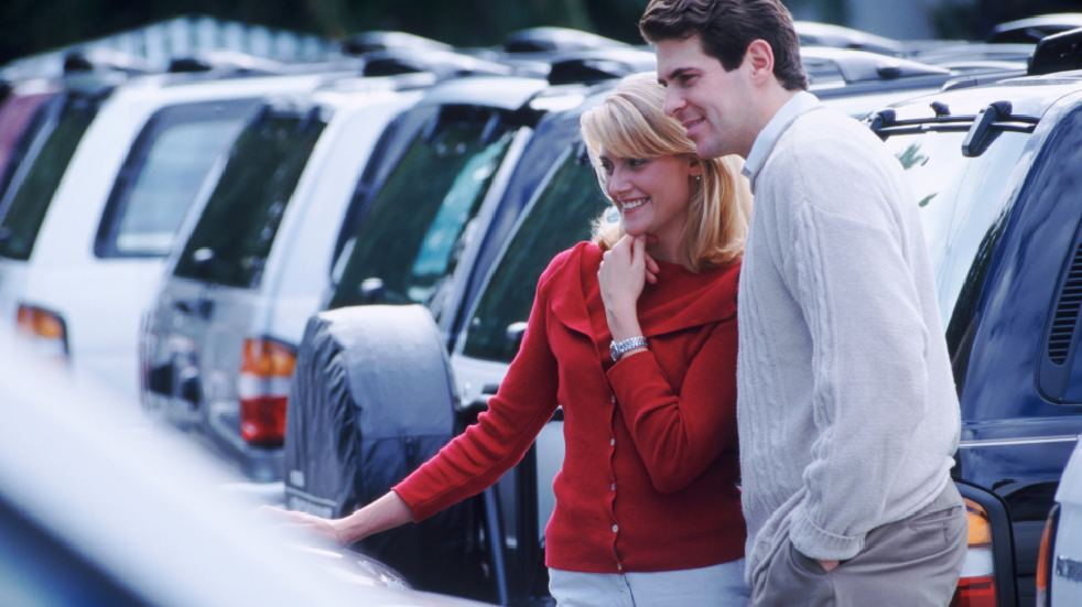 Should you buy a new or secondhand car couple looking at cars