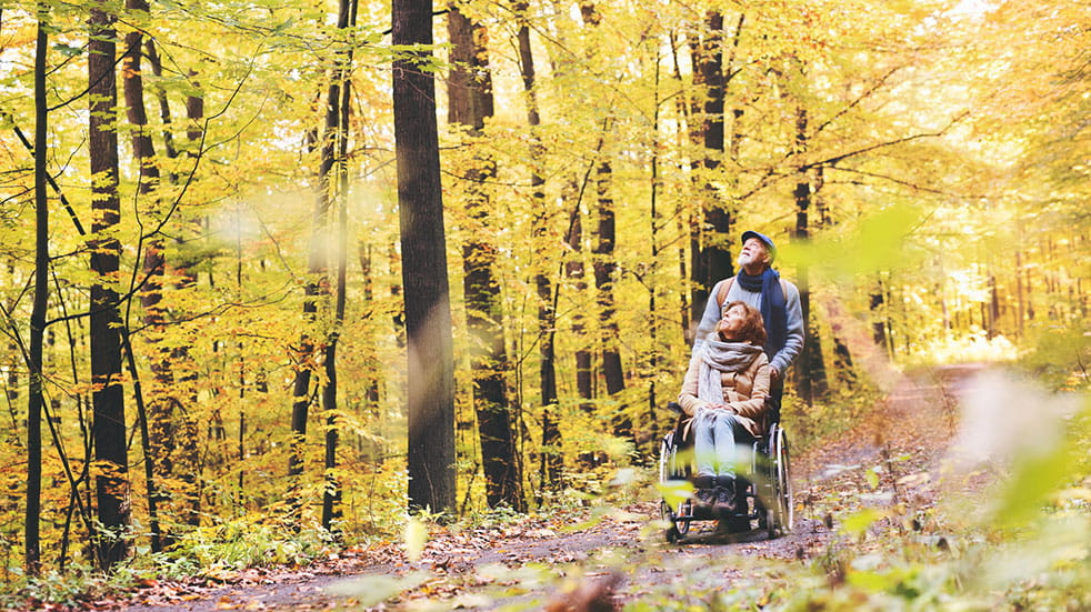 Six of the best European travel destinations man pushing woman in wheelchair through forest