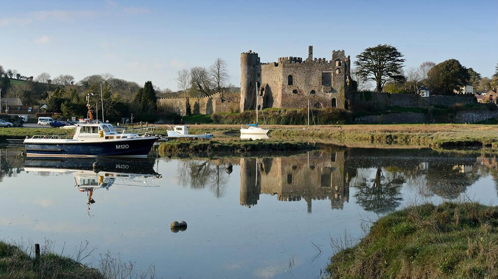 Laugharne Castle with a small boat in front