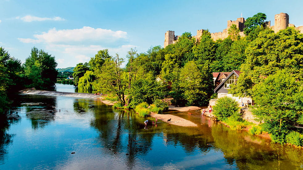Beautiful calm scene of the River Teme with the Medievil Ludlow castle partially shrouded amongst trees