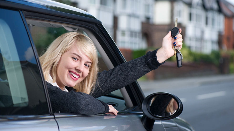 When is the best time of year to buy a new car woman smiling with car keys