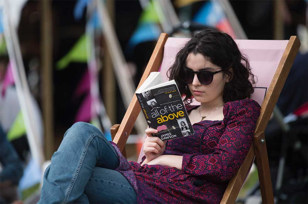 Young woman reading in a deckchair at Hay-on-Wye festival