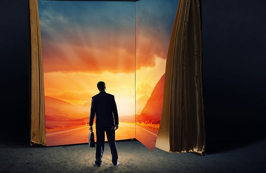 Silhoutte of a man standing in front of a book with a sunrise inside