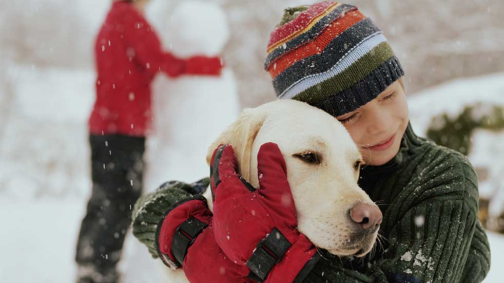 Protect your home and pets this winter child hugging dog snow