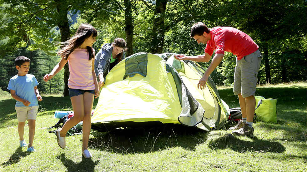 A Family putting up a tent in the forest