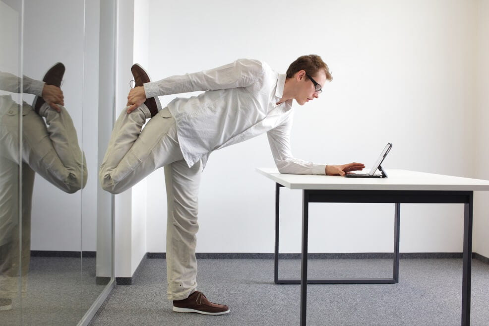 Man standing up and stretching at his desk