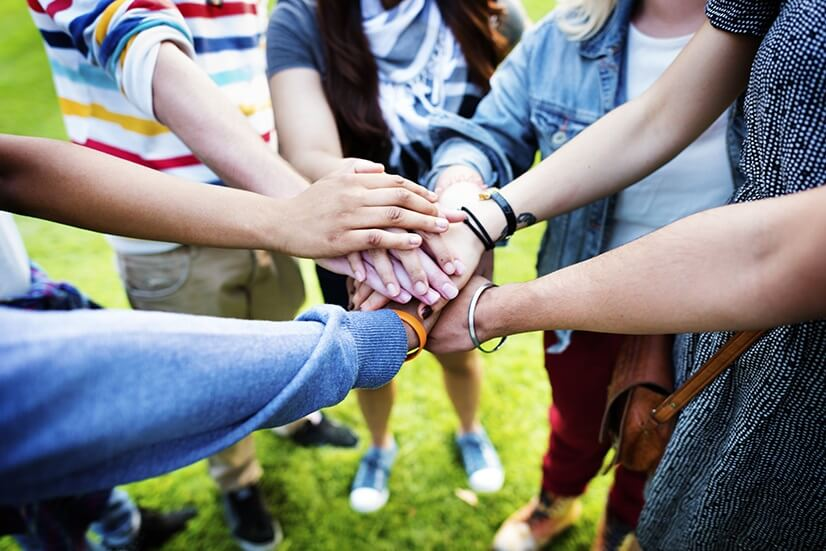 A group of people standing in a circle putting their hands together in the middle