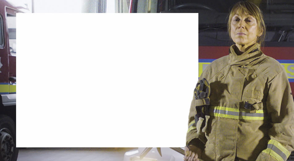 Firefighter standing on front of fire engine