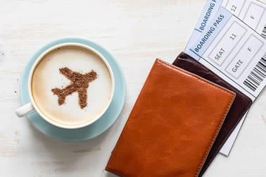 Wallet on a table with flight tickets and a mug of coffee
