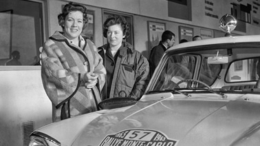 2 women standing by a sports car