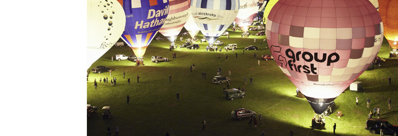 A collection of hot air balloons taking off at night
